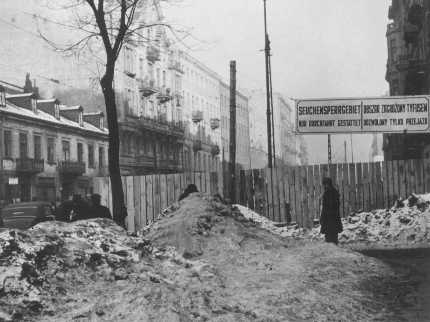 """Entrance to the Warsaw ghetto. The sign states: """"Epidemic Quarantine Area: Only Through Traffic is Permitted."""" Warsaw, Poland, February 1941."""