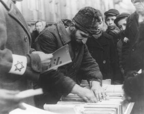 Un venditore ambulante al suo banco di vecchi libri in Hebrew. Ghetto di Varsavia, Polonia, febbraio 1941.