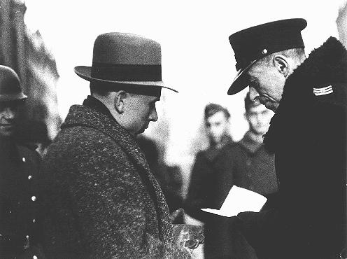 Un policía polaco revisa los documentos de un residente judío del ghetto. Varsovia, Polonia, febrero de 1941.