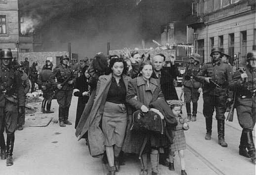 German soldiers lead Jews captured during the Warsaw ghetto uprising to the assembly point for deportation. Poland, May 1943.
