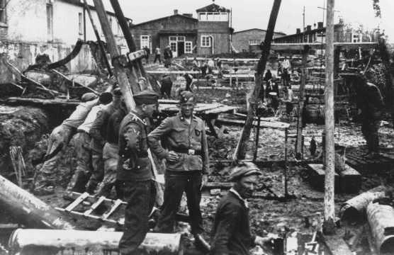 Des SS surveillent des travailleurs forcés réalisant des travaux de construction. Camp de concentration de Neuengamme, Allemagne, hiver 1943.