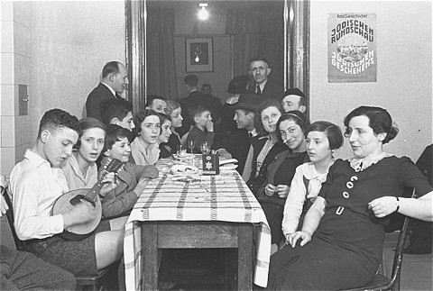 Members of the Chug Ivri (Hebrew Club) in Berlin celebrate Purim with food and song. On the wall is an advertisement for Juedische Rundschau, the newspaper of the German Zionist movement. Berlin, Germany, 1935.