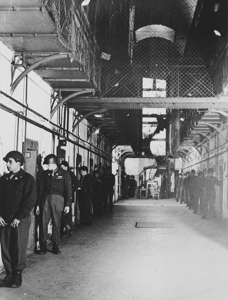 Vista de un ala de la prisión de Núremberg, que aloja a los acusados de los juicios por crímenes de guerra. Guardias bálticos bajo la supervisión de autoridades estadounidenses patrullan el ala y vigilan constantemente a los prisioneros. Los pisos superiores están separados con alambrera gruesa para disuadir a los prisioneros de intentos de suicidio. Núremberg, Alemania, entre el 20 de noviembre de 1945 y el 1 de octubre de 1946.