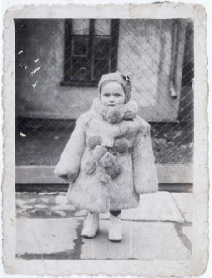 Portrait of three-year-old Estera Horn wrapped in a fur coat. Chelm, Poland, ca. 1940. Estera was born in January 1937. Her father was killed soon after the Germans invaded Poland. Estera and her mother, Perla Horn, were forced into the ghetto in Chelm. At the end of 1942, during the liquidation of the ghetto, Perla and Estera escaped from the ghetto. They hid in nearby villages. In late 1943, Perla asked a family in Plawnice to take care of Estera. Perla tried to hide with a group of Jews in the nearby forest, but they were discovered by Germans and killed. In the spring of 1944, the family began looking for a new home for Estera (who had been given the name Marysia). She was placed in Warsaw, and eventually transferred to an orphanage in Krakow.