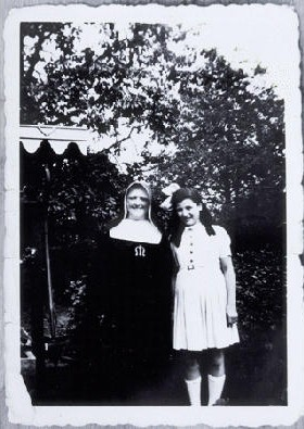 Augusta Feldhorn stands next to a nun while in hiding. Augusta, a Jewish child, was in hiding under an assumed Christian identity. Belgium. 1942-1945.