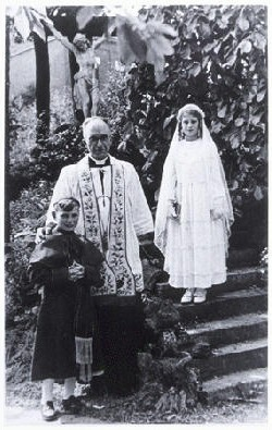 "Some Jewish children survived the Holocaust because they were protected by people and institutions of other faiths. Children quickly learned to master the prayers and rituals of their ""adopted"" religion in order to keep their Jewish identity hidden from even their closest friends. This photograph shows two hidden Jewish children, Beatrix Westheimer and her cousin Henri Hurwitz, with Catholic priest Adelin Vaes, on the occasion of Beatrix's First Communion. Ottignies, Belgium, May 1943."
