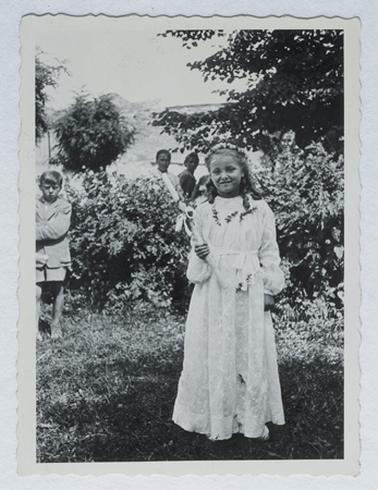Selma Schwarzwald poses outside while wearing her first communion dress. Selma lived in hiding as a Polish Catholic during the war. Busko-Zdroj, Poland, 1945.