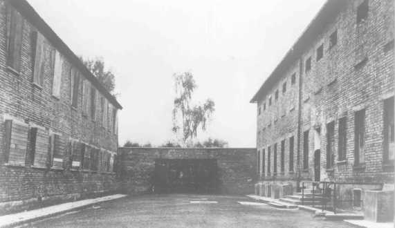 آشوٹز حراستی کیمپ میں بلاک 10 (بائیں) اور بلاک 11 (دائیں) کے درمیان سیاہ دیوار جہاں قیدیوں کو پھانسی دی جاتی تھی۔ پولنڈ، تاریخ نامعلوم۔