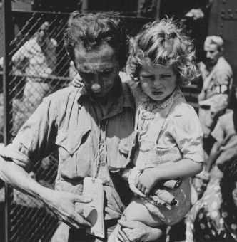 Jewish refugees from Europe arrive at the emergency refugee shelter at Fort Ontario. A father, holding his daughter, checks his tags. Oswego, New York, United States, August 4, 1944.