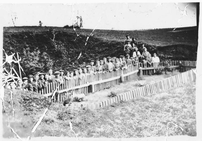 أعضاء فرقة الفدائيين بيلسكي جنب مقبرة جماعية بعد التحرير. بولندا 1945.