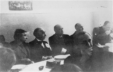 A meeting of the Warsaw Jewish council. Sitting behind table, 2nd to 4th from left: industrialist Abraham Gepner; chairman Adam Czerniakow; and lawyer Gustav Wielikowski. Warsaw, Poland, between 1939 and 1942.