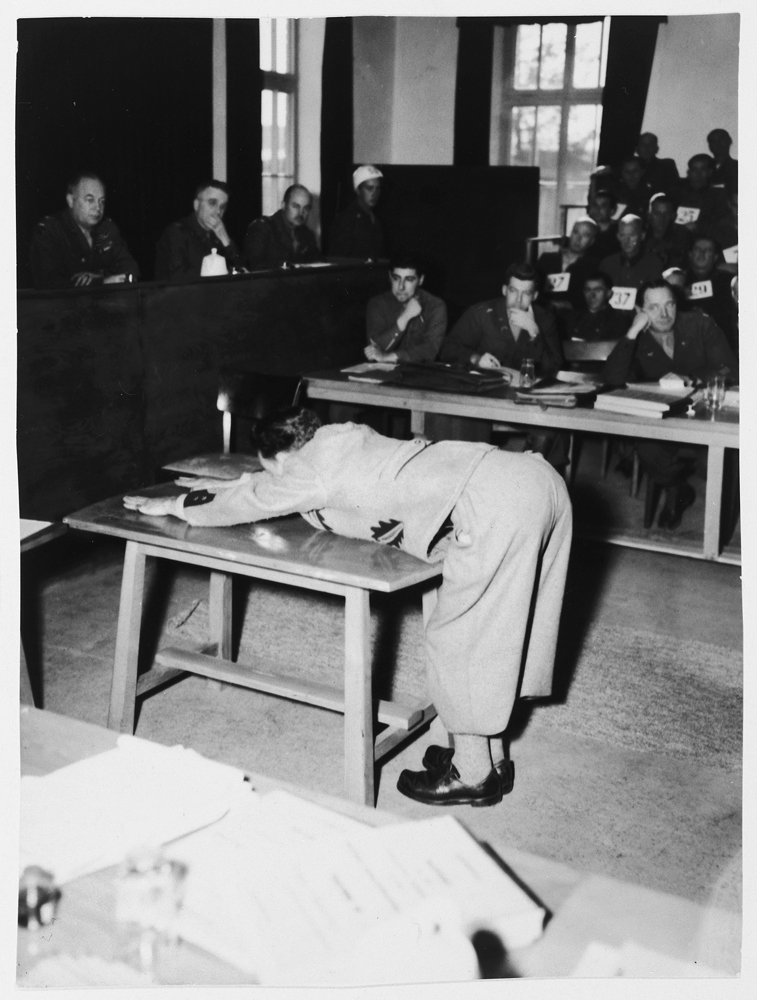 A prosecution witness demonstrates the position prisoners were forced to assume for punishment on the whipping block in the Dachau concentration camp.