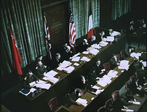 The International Military Tribunal was a court convened jointly by the victorious Allied governments.  Here  the Soviet, British, American, and French flags hang behind the judges' bench.