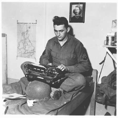 US Army Signal Corps photographer J Malan Heslop types photo captions. France, 1944.