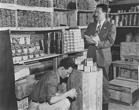 Morris Laub (right), Joint Distribution Committee director for Cyprus, reviews supplies sent for the 12,000 Jews still interned on the island. Cyprus, December 9, 1948.