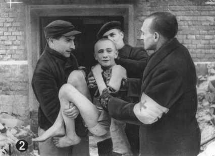 Soon after liberation, an emaciated child survivor is carried out of camp barracks by Soviet first-aid workers. Auschwitz, Poland, after January 27, 1945.