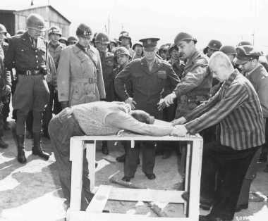 A survivor shows US Generals Eisenhower, Patton, and Bradley how inmates at Ohrdruf camp were tortured. Ohrdruf, Germany, April 1945.