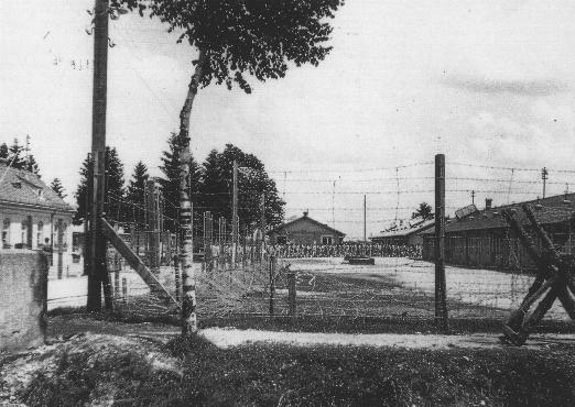 An early view of the Dachau concentration camp. Columns of prisoners are visible behind the barbed wire. Dachau, Germany, May 24, 1933.