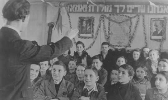 Paroles de l'hymne national juif et portraits des dirigeants sionistes accrochés dans une classe. Camp de personnes déplacées de Feldafing, Allemagne, après avril 1945.