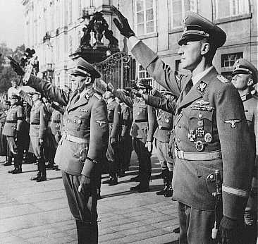 Reinhard Heydrich (right) and his deputy, Karl Hermann Frank (center), stand at attention during Heydrich's inauguration as governor of the Protectorate of Bohemia and Moravia. Prague, September 1941.