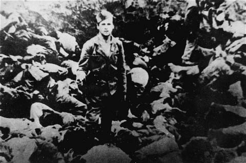 A Ustasa (Croatian fascist) guard stands amid corpses at the Jasenovac concentration camp, Yugoslavia, 1942.