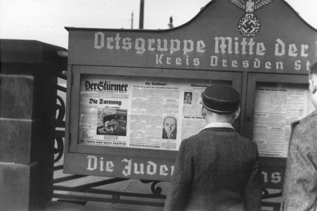 "German boys read an issue of Der Stuermer newspaper posted in a display box at the entrance to a Nazi party headquarters in the Dresden region. The German slogan (partially obscured) at the bottom of the display box reads, ""The Jews are our misfortune."""