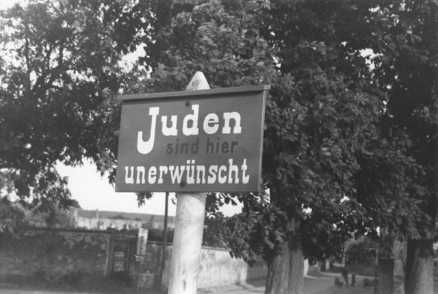 """An anti-Jewish sign posted on a street in Bavaria reads """"Jews are not wanted here."""" Germany, 1937."""