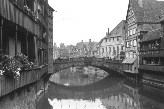 View of a bridge spanning a canal in Nuremberg. The houses and bridge are bedecked with Nazi flags and banners. Nuremberg, Germany, 1937.