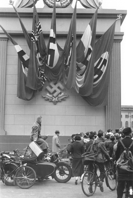 German spectators at a Nazi rally stand alongside a monument decorated with Nazi flags and a swastika emblem in Berlin. Germany, 1937.