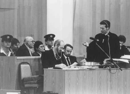 Chief defense attorney Mark O'Conner (standing) addresses a question to John Demjanjuk during Demjanjuk's trial. Jerusalem, Israel, Feburary 16, 1987.