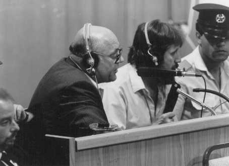 Defendant John Demjanjuk comments on documents being viewed on a large screen in court. Jerusalem, Israel, July 27, 1987.