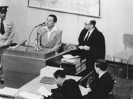 Henryk Ross testifies during Adolf Eichmann's trial. In addition to official duties as a photographer in the Department of Statistics in the Lodz ghetto, Ross secretly photographed scenes in the ghetto. To Ross' right is chief prosecutor Gideon Hausner, who holds some of Ross' photographs submitted as evidence. Jerusalem, Israel, May 2, 1961.
