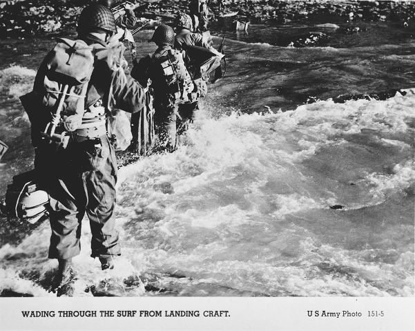 American troops wade through the surf on their arrival at the Normandy beaches on D-Day. Normandy, France, June 6, 1944.