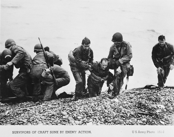 American troops pull the survivors of a sunken craft on to the shores of the Normandy beaches on D-Day. Normandy, France, June 6, 1944.