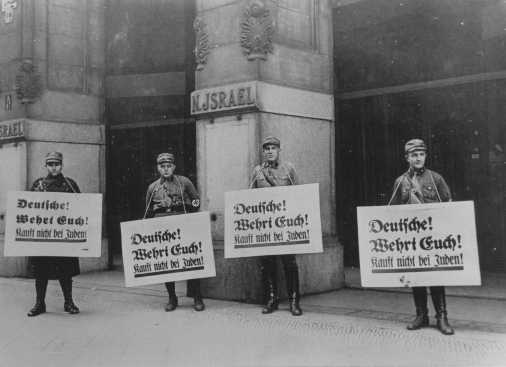 "SA men in front of Jewish-owned store urge a boycott with the signs reading ""Germans! Defend Yourselves! Don't buy from Jews!"" Berlin, Germany, April 1, 1933."