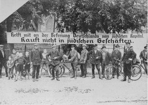 """لافتة تم استخدامها أثناء المقاطعة المعادية لليهود: """"ساعدوا في تحرير ألمانيا من الرأسمالية اليهودية. لا تشتروا من متاجر اليهود."""" ألمانيا، عام 1933."""