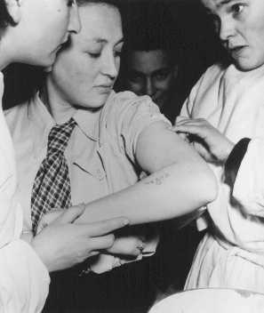 A former concentration camp prisoner receives care from a mobile medical unit of the United Nations Relief and Rehabilitation Administration. Bergen-Belsen displaced persons camp. Germany, May 1946.