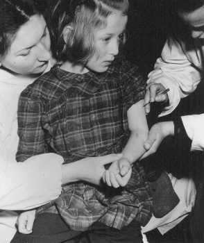 Birleşmiş Milletler personeli Auschwitz kampındaki tıbbî deneylerde kullanılan 11 yaşındaki sağ kalan çocuğa aşı yapıyor. Mayıs 1946, Bergen-Belsen zorla göç ettirilmiş insanlar kampı, Almanya.