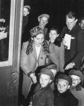A welfare officer of the United Nations Relief and Rehabilitation Administration (UNRRA) assists Polish Jewish orphans en route to France and Belgium. Prague, Czechoslovakia, probably 1946.