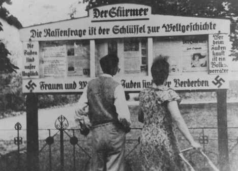 "A German couple reads an outdoor display of the antisemitic newspaper ""Der Stuermer"" (""The Attacker""). Germany, 1935."