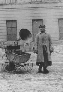 A Jewish man attempts to make a living by playing music on a gramophone, which he wheels around in an old baby carriage. Warsaw ghetto, Poland, wartime.