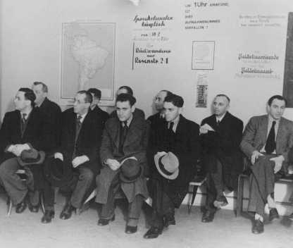 German Jews, seeking to emigrate, wait in the office of the Hilfsverein der Deutschen Juden (Relief Organization of German Jews). On the wall is a map of South America and a sign about emigration to Palestine. Berlin, Germany, 1935.
