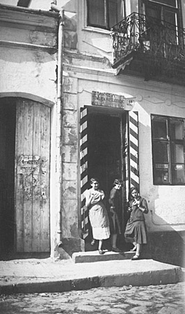 Malcia, Matla, and Rachel Saleschutz eat bagels in the doorway of their mother's store. The red and white stripes on the door frames indicated that the store carried cigarettes, matches, and sugar, consumer goods regulated by a state monopoly. Kolbuszowa, Poland, 1934.