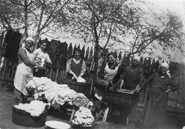 Members of the Saleschutz family do laundry in the yard of their home. Kolbuszowa, Poland, 1934.