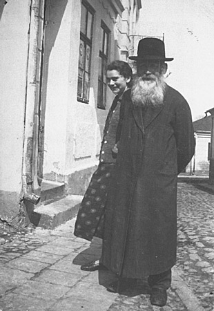 Isak Saleschutz and his daughter, Rachel, stand in front of their house. Kolbuszowa, Poland, 1937.