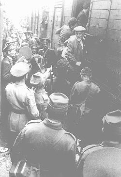 Police force Romanian Jews, survivors of a pogrom in Iasi, to board a train during their expulsion from Iasi to Calarasi. Iasi, Romania, late June 1941.