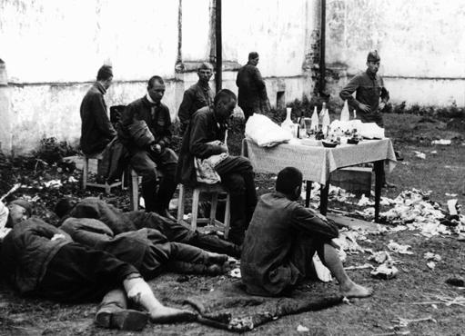 Wounded Soviet prisoners of war await medical attention. The German army provided only minimal treatment, and permitted captured Soviet personnel to care for their own wounded using only captured medical supplies. Baranovichi, Poland, wartime.