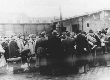 At the Jozsefvarosi train station in Budapest, Raoul Wallenberg (at right, with hands clasped behind his back) rescues Hungarian Jews from deportation by providing them with protective passes. Budapest, Hungary, 1944.