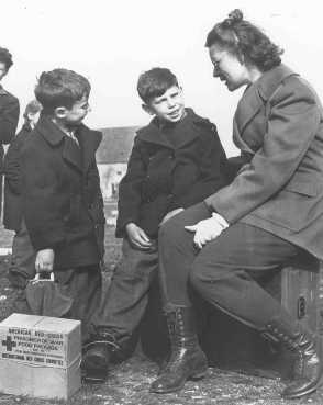 Jewish refugee children from Budapest talk to a worker from the United Nations Relief and Rehabilitation Administration. Germany, after May 1945.