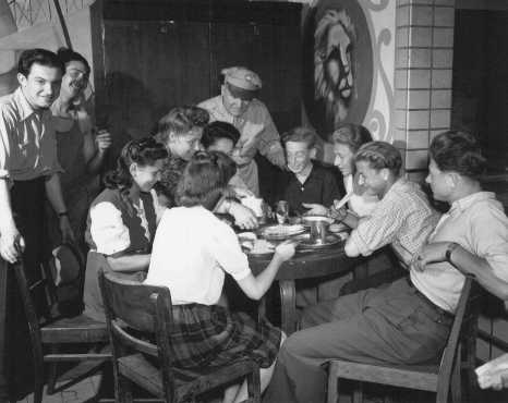 An officer of the United Nations Relief and Rehabilitation Administration (UNRRA) visits with a group of young refugees. Eschwege displaced persons camp, Germany, July 7, 1946.